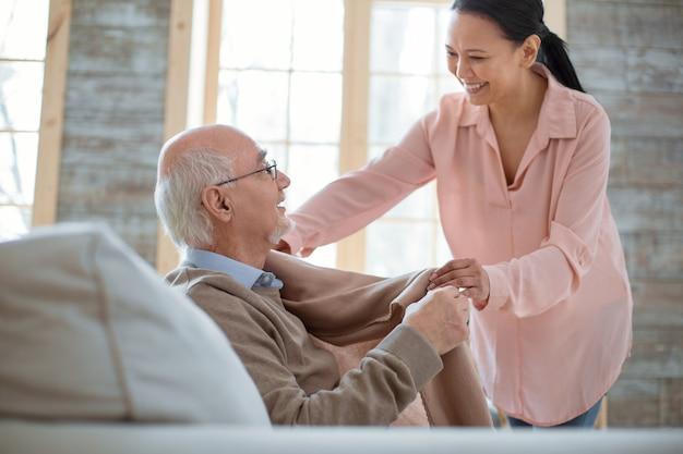 Primera conversación. atento cuidador amable de pie mientras sonríe y da manta al hombre mayor