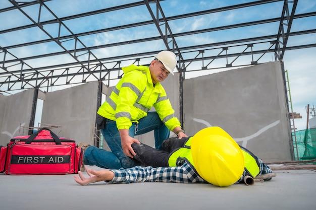 Primeros auxilios para accidentes de emergencia en obras. trabajador de la construcción resultó herido en una caída desde una altura en un sitio de construcción. los ingenieros ayudan en primeros auxilios, el equipo de seguridad ayuda a los empleados en accidentes.