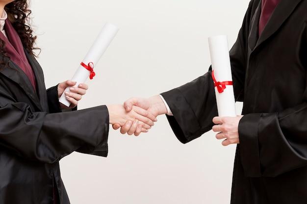 Primeros graduados dándose la mano