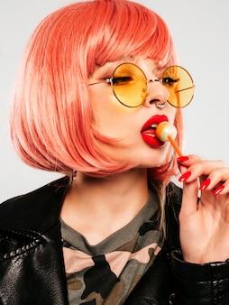 Primeros labios de la joven y bella chica mala inconformista en una chaqueta de cuero negro de moda y un arete en la nariz. mujer sonriente despreocupada y sexy posando en el estudio con peluca rosa. modelo positivo lamiendo caramelos redondos
