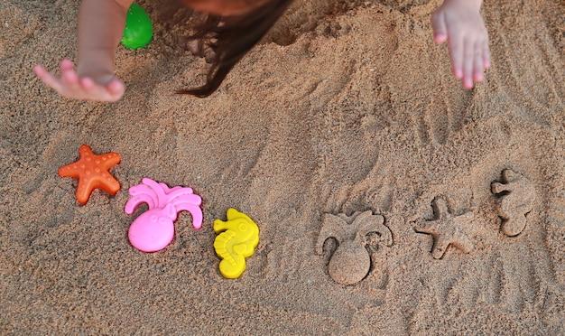 Primeros niños manos jugando arena con bloques animales formando en la playa.