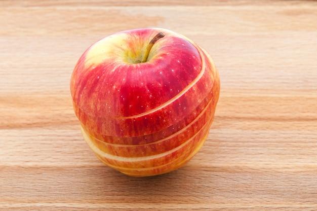 Los primeros planos de la manzana roja cortan por las tazas en una tabla de cortar de madera