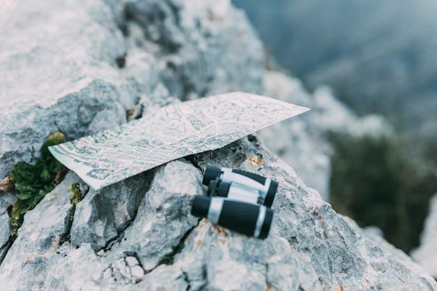 Prismáticos y mapa en roca