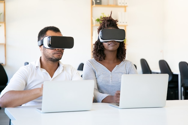 Probadores afroamericanos enfocados con gafas de realidad virtual en la oficina
