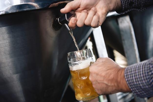 Probando la cerveza inglesa del tanque de acero inoxidable que vierte en la taza