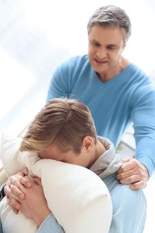 Problema adolescente está escondiendo su rostro en la almohada.