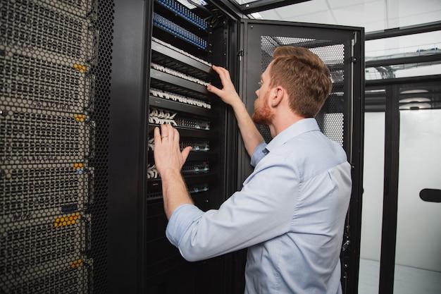 Problema de la computadora. técnico de ti seguro que examina el armario del servidor mientras está de pie