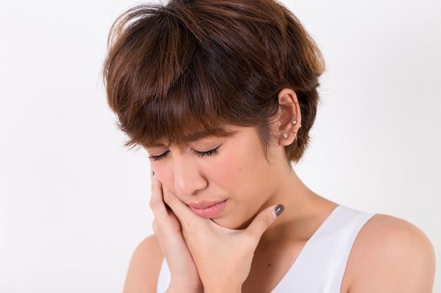 Problema con los dientes mujer que siente dolor de dientes aislado en el fondo blanco. iluminación de estudio. concepto para