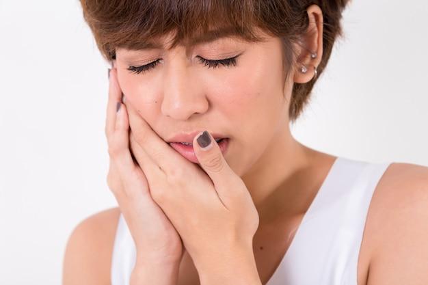 Problema de los dientes. mujer siente dolor de dientes. aislado en blanco estudio de iluminación. concepto de salud y medicina.