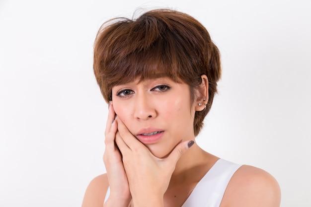 Problema de los dientes. mujer sintiendo dolor en los dientes. aislado en el fondo blanco iluminación de estudio. concepto para salud y medico.