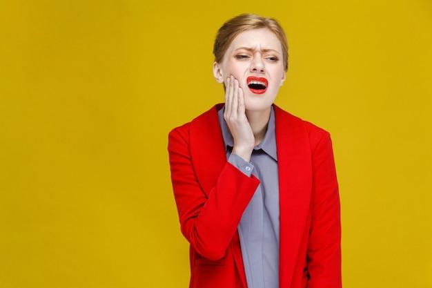 Problema de estomatología pelirroja mujer de negocios en traje rojo tiene dolor de dientes