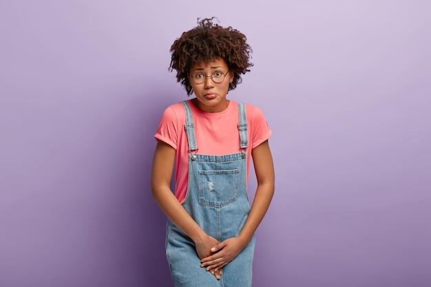 Problema médico, concepto de incontinencia. mujer afroamericana disgustada tiene la entrepierna, espera cerca del inodoro cerrado, necesita inodoro