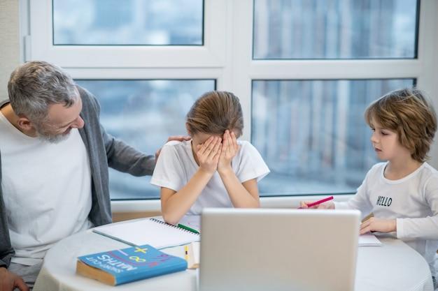 Problema. la niña cierra la cara y se ve molesta mientras el padre intenta calmarla.