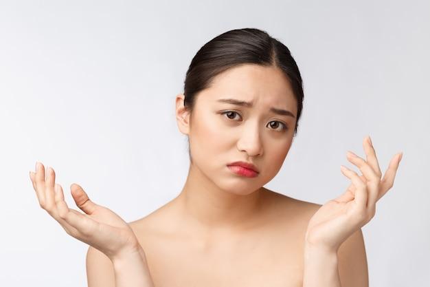 Problema de la piel de la cara: mujer joven infeliz toca su piel aislada, concepto para el cuidado de la piel, asiático