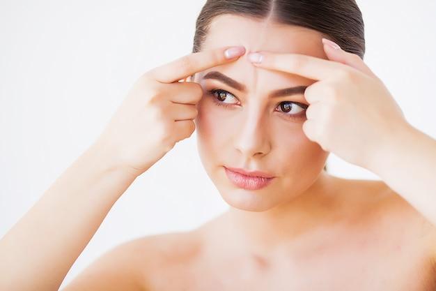 Problema de la piel. mujer aplastante en la cara y mirando en el espejo