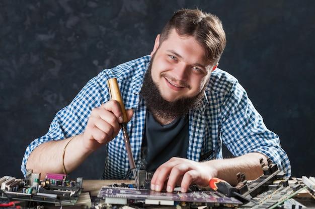 Problema de reparación de reparador con herramienta de soldadura. ingeniero repara componentes de computadora con soldador.