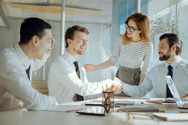 Problema resuelto. líder del equipo femenino cariñoso reconciliando a sus dos colegas masculinos durante la reunión y riendo y dándose la mano