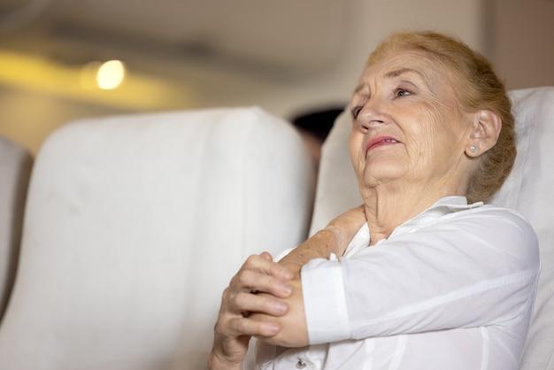 Problema de salud en un avión, la pasajera senior en el avión sintió dolor en el hombro debido a un largo viaje en avión