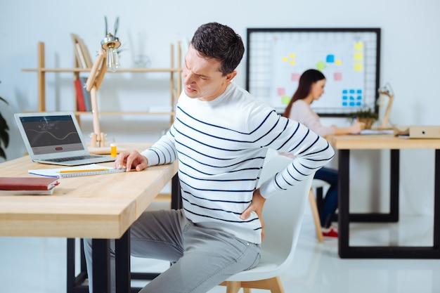 Problema de salud. varón joven poniendo la mano izquierda en la espalda e inclinando la cabeza mientras está sentado en su lugar de trabajo