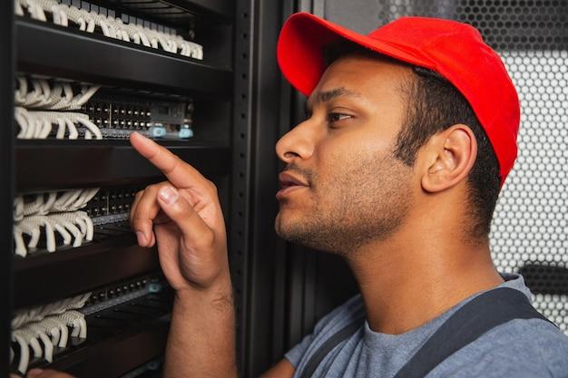 Problema de ti. ingeniero de ti nostálgico ponting con el dedo mientras mira el armario del servidor