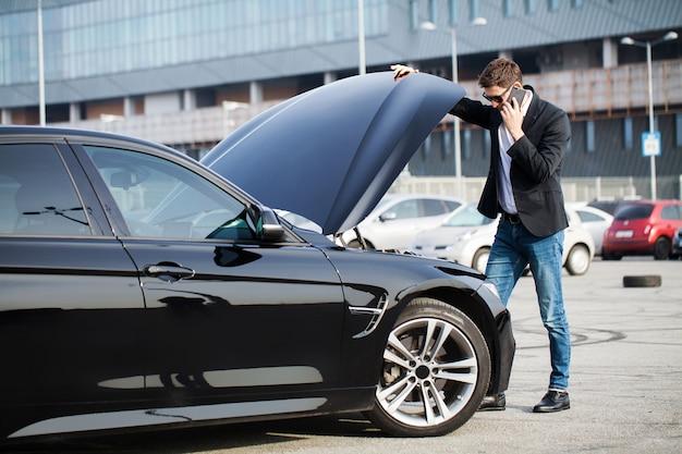 Problemas en el camino. hombre con auto roto llamando por teléfono inteligente