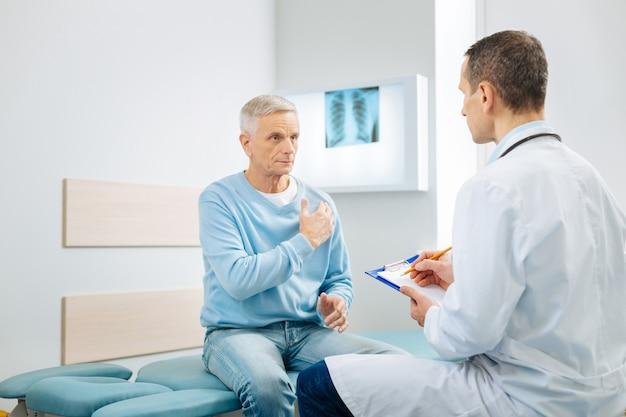 Problemas del corazón. agradable agradable hombre serio mirando a su médico y apuntando al corazón mientras habla de su problema de salud