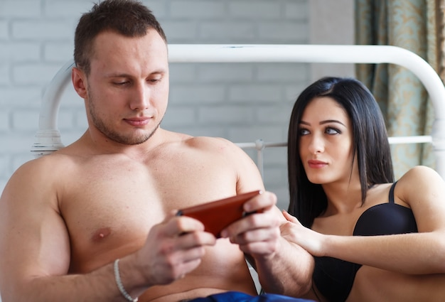 Problemas en la familia. mujer joven enojada acostada en la cama, contra su marido, que juega el juego en el teléfono.