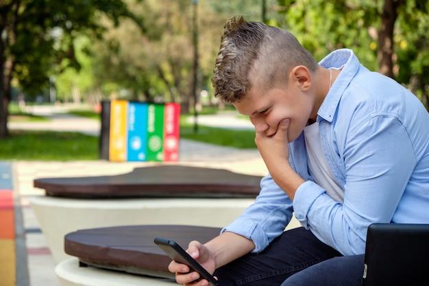 Problemas de los niños modernos. chico joven en el parque con el teléfono molesto