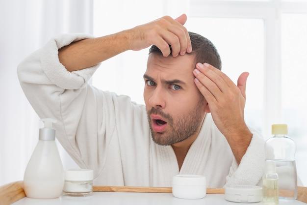 Problemas de la piel. hombre guapo infeliz que encuentra algunos problemas en la piel mientras examina su rostro