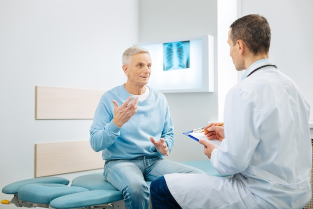 Problemas de salud. agradable y agradable anciano sentado en la cama y gesticulando mientras le cuenta al médico sobre su problema.