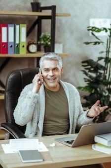 Problemas de trabajo. buen hombre positivo hablando por teléfono mientras está sentado en su oficina