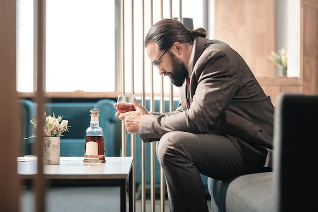 Problemas en el trabajo. hombre barbudo de pelo oscuro que se siente fatal después de problemas en el trabajo y beber alcohol