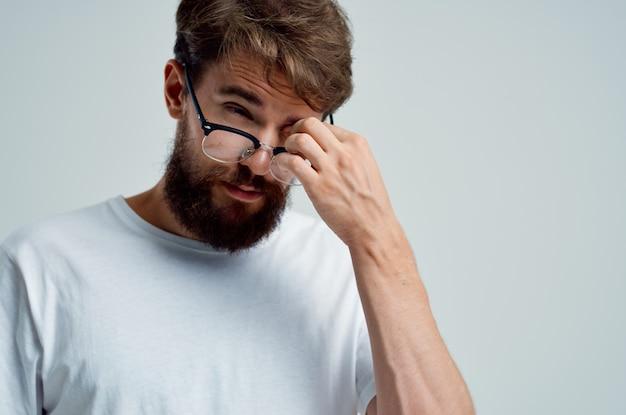Problemas de visión del hombre barbudo en primer plano de camiseta blanca