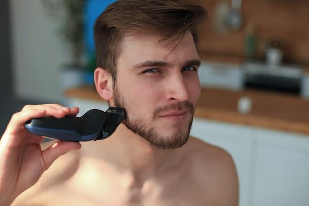 Procedimiento de afeitado. apuesto joven afeitándose la cara con afeitadora eléctrica mientras está de pie frente al espejo.
