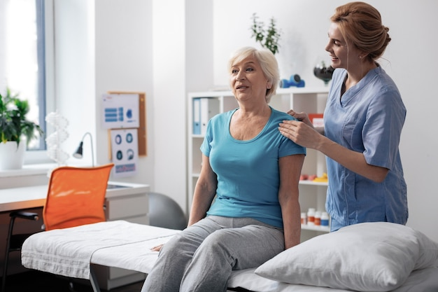 Procedimiento agradable. mujer de edad positiva sonriendo mientras recibe masaje profesional