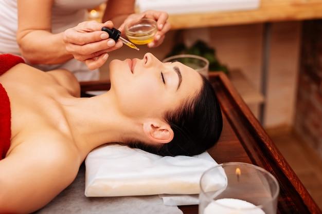 Durante el procedimiento. amable maestro profesional que le da a su cliente un aceite perfumado que huele y absorbe