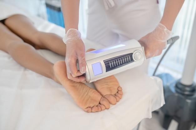 Procedimiento de corrección corporal. manos del médico con dispositivo de corrección corporal sobre los pies del paciente acostado en el sofá blanco