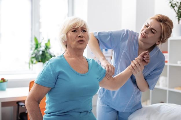 Procedimiento doloroso. agradable mujer de edad expresando sus emociones mientras se somete a un doloroso procedimiento de masaje