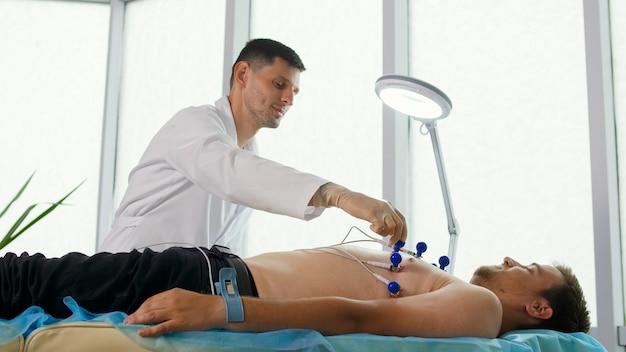 Procedimiento de electrocardiograma para diagnosticar enfermedades cardíacas. un cardiólogo coloca electrodos en el pecho desnudo de un joven acostado en el sofá para tomar un electrocardiograma en el consultorio de la clínica.