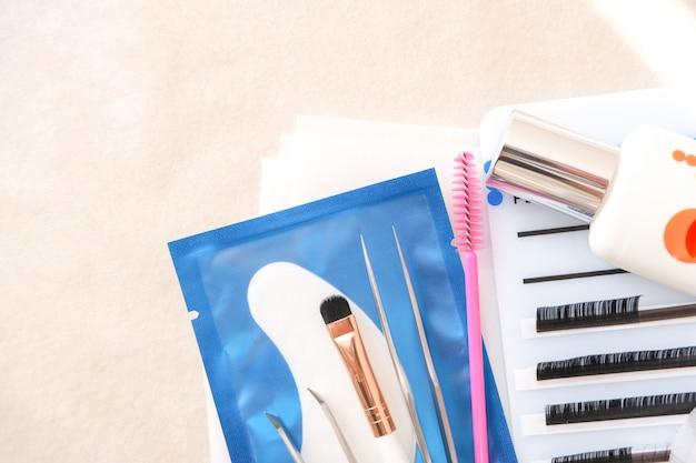 Procedimiento de extensión de pestañas. herramientas. pegamento, pinzas, pinceles. salón de belleza, moda y mujer conforman concepto.