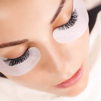 Procedimiento de extensión de pestañas. ojo de mujer con pestañas largas.