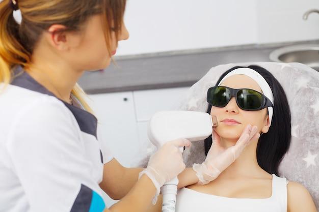 Procedimiento de microdermabrasión. exfoliación mecánica, pulido de diamantes. modelo y doctor. clínica cosmetológica. salud, clínica, cosmetología.