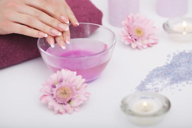 Procedimiento de spa, mujer en salón de belleza con dedos en baño de aroma para manos