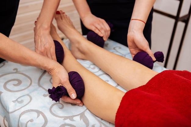 Procedimiento suave. maestras que usan bolsas de hierbas especiales para un masaje útil mientras las colocan en la parte inferior de las piernas