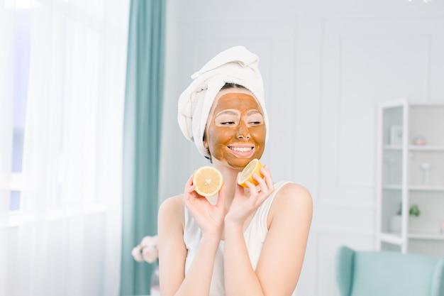Procedimientos de belleza concepto de cuidado de la piel. mujer joven con máscara de arcilla de barro facial marrón en la cara en el baño, con una toalla blanca en la cabeza, sosteniendo mitades de limón