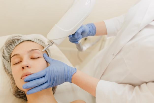 Procedimientos de cosmetología, rejuvenecimiento de mujer joven y bonita en salón de belleza. procedimiento de dermatología, manos en resplandor azul, en el trabajo, atención médica, terapia, botox, inyecciones