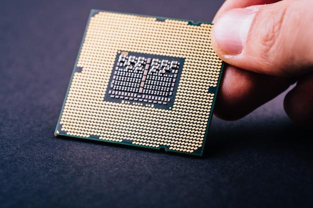 Procesador de la cpu chip de computadora sobre fondo negro oscuro sosteniendo en la mano