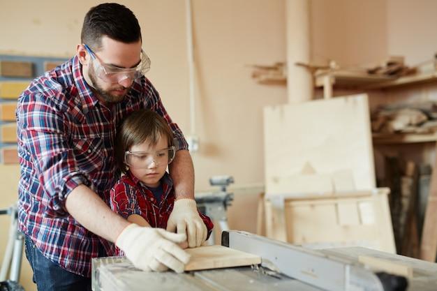 Procesando pieza de trabajo, padre e hijo trabajando con madera