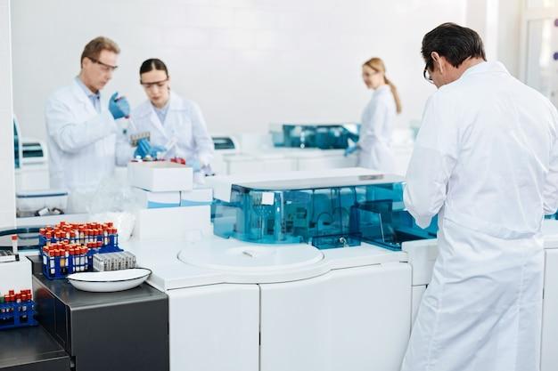 Proceso activo. dos colegas de pie cerca del soporte de vidrio inclinando la cabeza mientras examinan la sangre