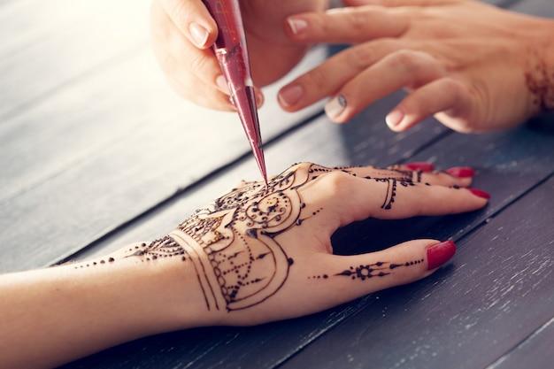Proceso de aplicación de mehndi en manos femeninas